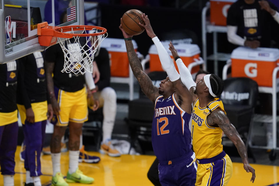 Los Angeles Lakers guard Kentavious Caldwell-Pope (1) defends against Phoenix Suns forward Torrey Craig (12) during the second quarter of Game 6 of an NBA basketball first-round playoff series Thursday, Jun 3, 2021, in Los Angeles. Caldwell-Pope was charged with a flagrant foul. (AP Photo/Ashley Landis)