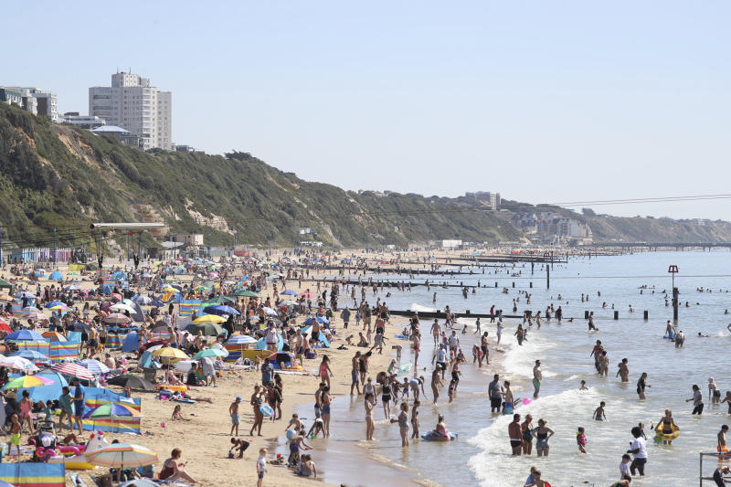 People gather on the beach at Bournemouth, Southern England, Friday Aug. 7, 2020. The UK could see record-breaking temperatures with forecasters predicting Friday could be the hottest day of the year. (Andrew Matthews/PA via AP)