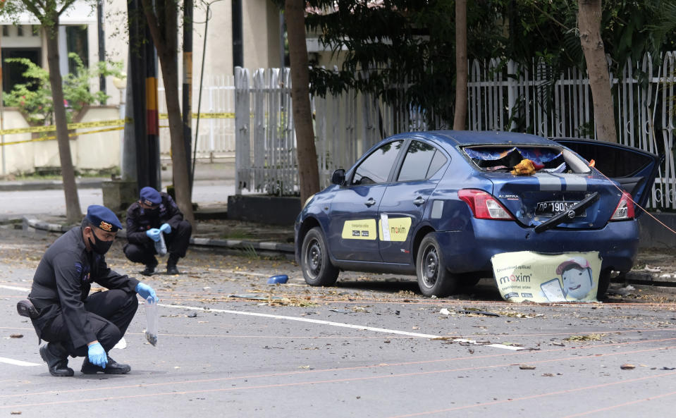 Police officers collect evidence from around the site of a bomb attack at the Sacred Heart of Jesus Cathedral in Makassar, South Sulawesi, Indonesia, Monday, March 29, 2021. Two attackers believed to be members of a militant network that pledged allegiance to the Islamic State group blew themselves up outside the packed Roman Catholic cathedral during a Palm Sunday Mass on Indonesia's Sulawesi island, wounding a number of people, police said. (AP Photo/Masyudi S. Firmansyah)