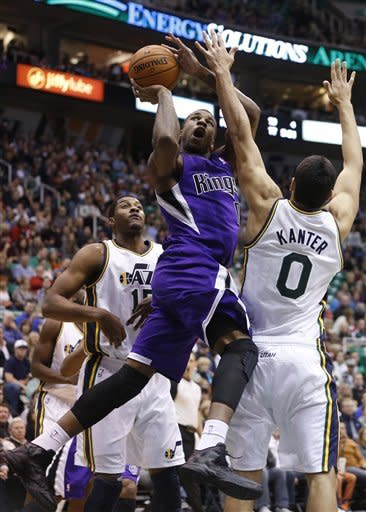Sacramento Kings forward Thomas Robinson, center, shoots while defended by Utah Jazz forward Derrick Favors, left, and center Enes Kanter (0), of Turkey, during the first half of their NBA basketball game in Salt Lake City, Friday, Nov. 23, 2012. (AP Photo/Jim Urquhart)