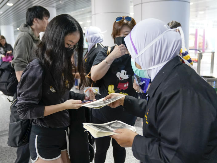 Health officials hand out information about the current coronavirus at Kuala Lumpur International Airport in Sepang, Malaysia, Tuesday, Jan. 21, 2020. Countries both in the Asia-Pacific and elsewhere have initiated body temperature checks at airports, railway stations and along highways in hopes of catching those at risk of carrying a new coronavirus that has sickened more than 200 people in China. (AP Photo/Vincent Thian)