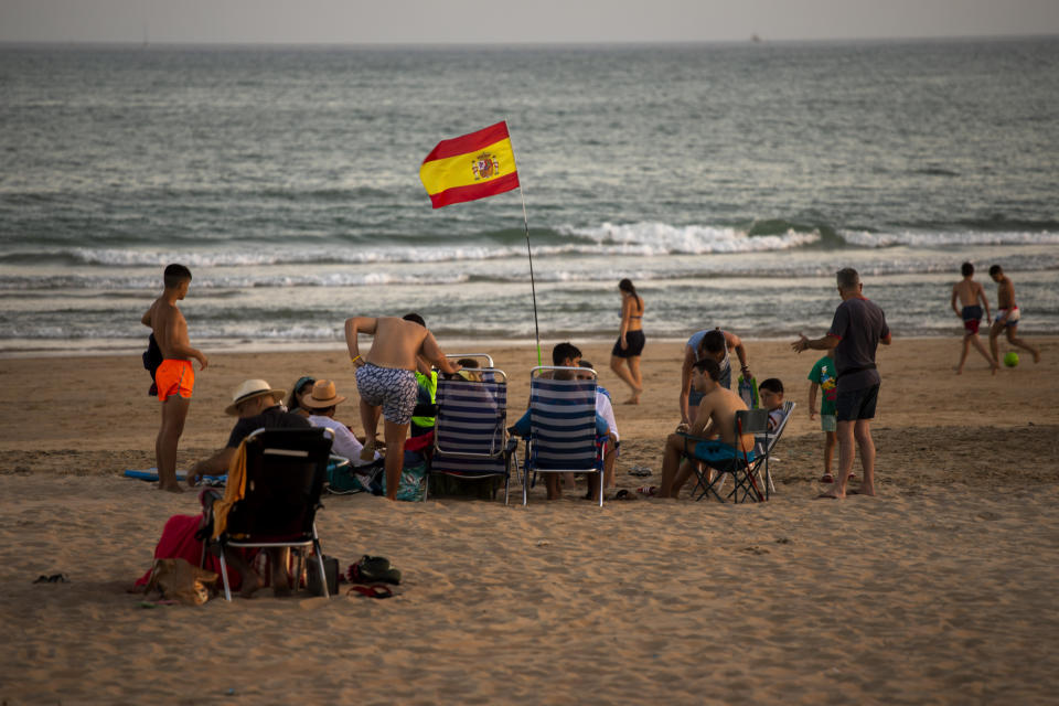 A Spanish flag waves as bathers enjoy the beach in Barbate, Cadiz province, south of Spain, on Saturday, July 25, 2020. Ministers are set to remove Spain from the Government's list of safe countries to travel to after the European country saw a rise in Covid-19 cases. The decision means those coming back from Spain will have to self-isolate for two weeks upon their return to England. (AP Photo/Emilio Morenatti)