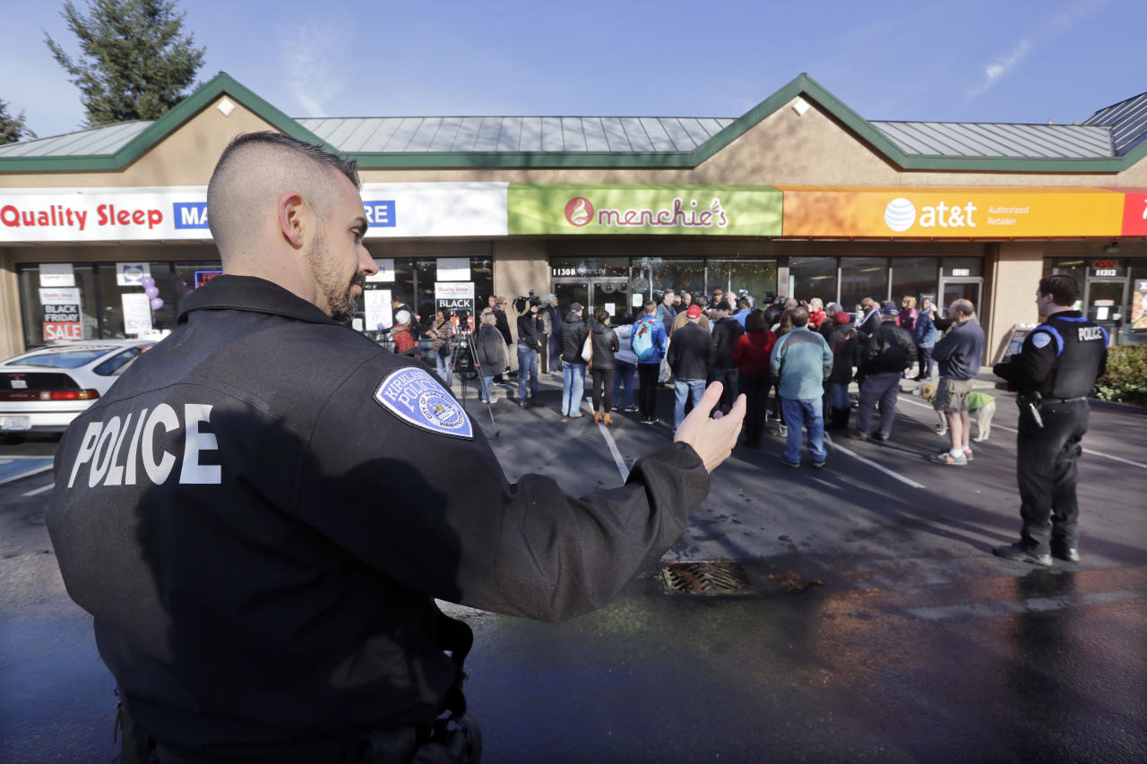 A Kirkland police officer directs traffic past a closed frozen-yogurt shop where Byron Ragland and local civil rights leaders addressed media members Tuesday, Nov. 20, 2018, in Kirkland, Wash. The police department there has apologized for an incident in which officers helped the owner of the Menchie's shop expel Ragland, an African-American man, from the business because employees said they felt uncomfortable. The Seattle Times reported that the shop's owner called police on Nov. 7 about Ragland, who works as a court-appointed special advocate, who was in the shop supervising a court-sanctioned outing between a mother and her son. (AP Photo/Elaine Thompson)