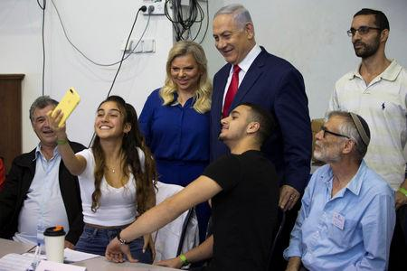 A youth takes a selfie with Israel's Prime Minister Benjamin Netanyahu and his wife Sara after they voted in Israel's parliamentary election in Jerusalem April 9, 2019. Ariel Schalit/Pool via REUTERS