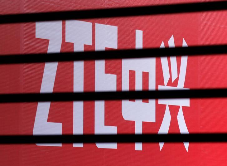 FILE PHOTO: The company logo of ZTE is seen through a wooden fence on a glass door during the company's 15th anniversary celebration in Beijing