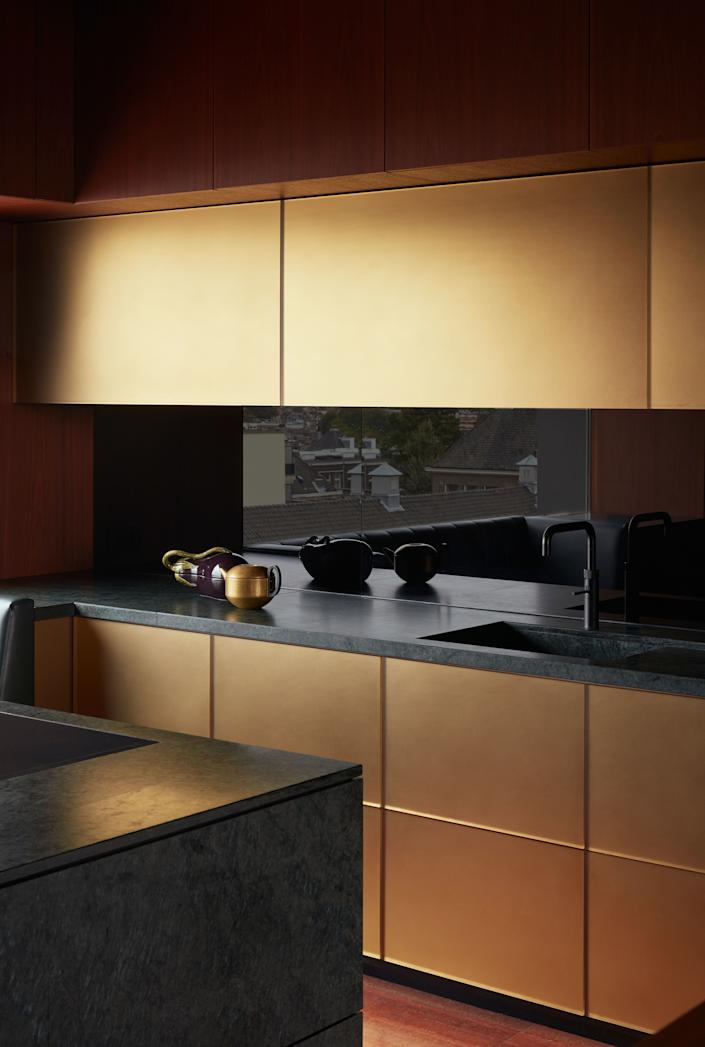 """<div class=""""caption""""> The kitchen is an homage to Rotterdam's midcentury-modern architecture of the post-war reconstruction era. The counter is made of Italian green <em>serpentino</em> stone, the cabinets of Mahogany wood, and the black backsplash is painted glass. The gold resin cabinets cast a warm, golden light in the kitchen. </div>"""