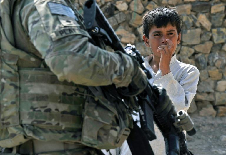 An Afghan youth looks at a US soldier in Nangarhar province of Afghanistan in 2011