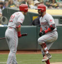 Cincinnati Reds' Eugenio Suarez, right, celebrates with Derek Dietrich (22) after hitting a home run off Oakland Athletics' Chris Bassitt in the third inning of a baseball game Thursday, May 9, 2019, in Oakland, Calif. (AP Photo/Ben Margot)