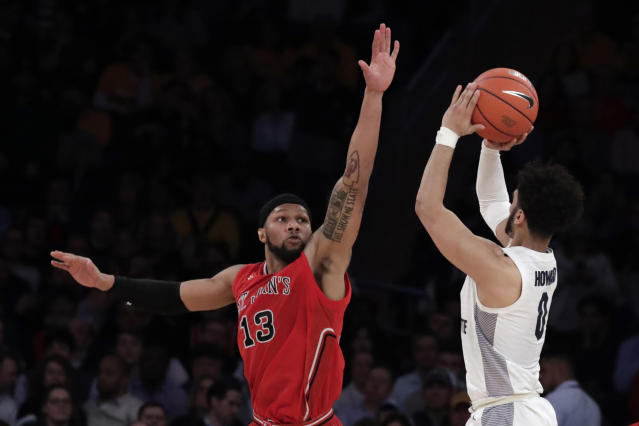 Marquette guard Markus Howard (0) shoots a against St. John's forward Marvin Clark II (13) during the second half of an NCAA college basketball game in the Big East men's tournament, Thursday, March 14, 2019, in New York. Marquette won 86-54. (AP Photo/Julio Cortez)