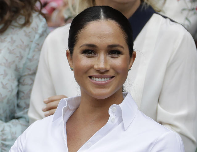 """FILE - In this July 13, 2019 file photo, Kate, Meghan, Duchess of Sussex smiles while sitting in the Royal Box on Centre Court to watch the women's singles final match between Serena Williams, of the United States, and Romania's Simona Halep on at the Wimbledon Tennis Championships in London. Meghan has guest edited the September issue of British Vogue with the theme """"Forces for Change."""" Royal officials say the issue coming out Aug. 2 features """"change-makers united by their fearlessness in breaking barriers"""" and includes a conversation between Meghan and former U.S. first lady Michelle Obama. (AP Photo/Ben Curtis, File)"""