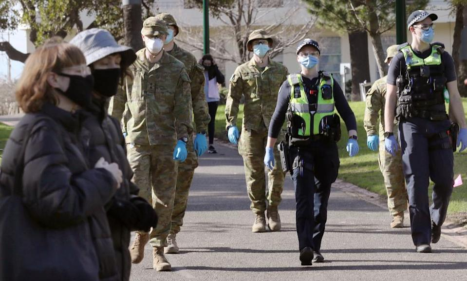 Australian Defence Force personnel and Victoria police officers patrol Fitzroy Gardens in Melbourne