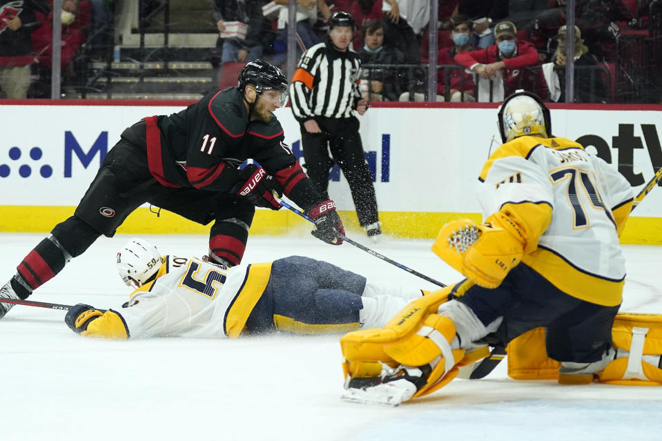 Carolina Hurricanes center Jordan Staal (11) tries to score against Nashville Predators goaltender Juuse Saros (74) while Predators defenseman Roman Josi (59) defends during the second period in Game 1 of an NHL hockey Stanley Cup first-round playoff series in Raleigh, N.C., Monday, May 17, 2021. (AP Photo/Gerry Broome)