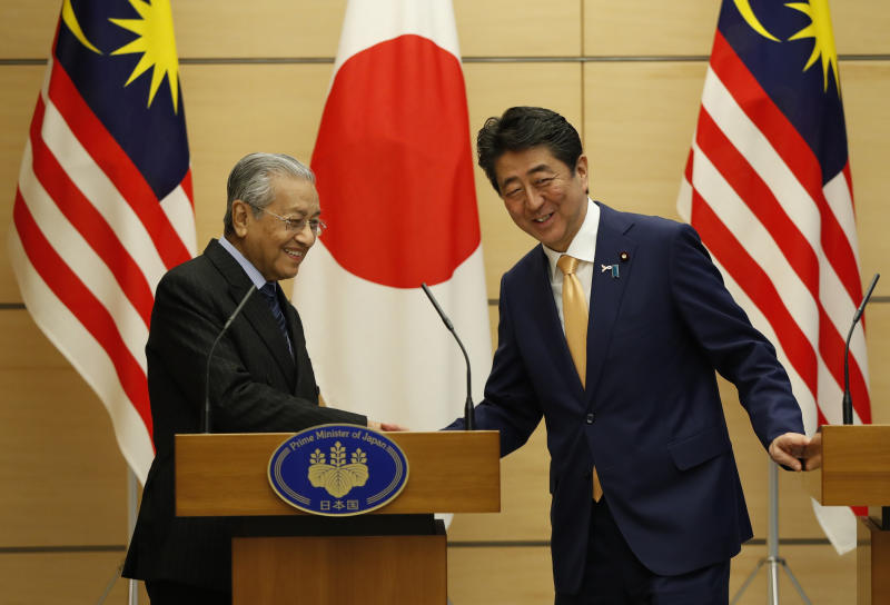 Malaysia's Prime Minister Mahathir Mohamad exchanges smiles with Japan's Prime Minister Shinzo Abe at the end of their joint news conference at Abe's official residence in Tokyo, Tuesday, Nov. 6, 2018. (Issei Kato/Pool Photo via AP)