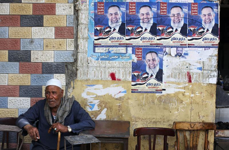 "An Egyptian man smokes at a café beneath campaign posters for former presidential candidate Hazem Abu Ismail in central Cairo, Egypt, Sunday, April 30, 2012. The Arabic on the poster reads, ""Hazem Salah for Egyptian Presidency."" (AP Photo/Fredrik Persson)"