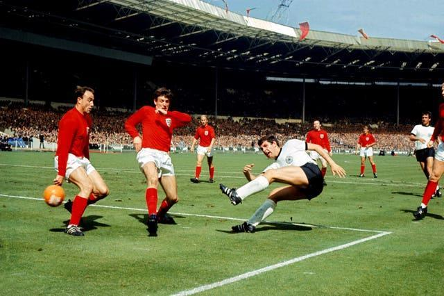 West Germany's Lothar Emmerich (fourth l) fires a shot past England's George Cohen (l)
