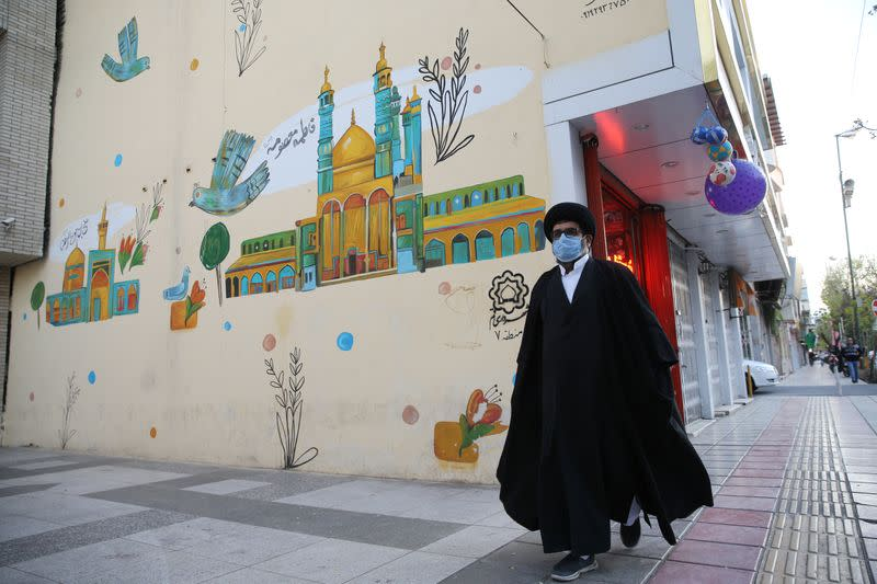 A cleric wearing a protective face mask, following the outbreak of coronavirus disease (COVID-19), walks on the street in Qom