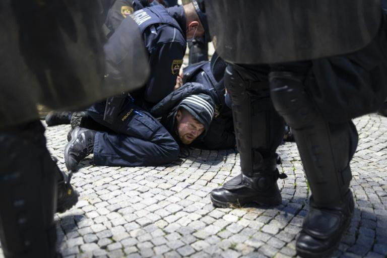 Police officers hold down a protester during a rally against coronavirus restrictions in Ljubljana, Slovenia