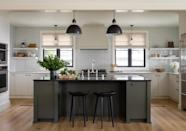 """<p>Breaking from the black-and-white scheme seen throughout the rest of the home, <a href=""""https://www.marthastewart.com/1502463/kitchen-design-ideas"""" rel=""""nofollow noopener"""" target=""""_blank"""" data-ylk=""""slk:the green island is the kitchen's focal point"""" class=""""link rapid-noclick-resp"""">the green island is the kitchen's focal point</a>. This was intentional, says Beers, who notes that tackling the overall color palette was an involved process: """"Light in the Pacific Northwest is very particular, and when you combine that with a strong waterfront exposure, it is hard to get a white house to feel cozy and nice,"""" he explains. """"We tested a lot of color and ended up with a very warm, creamy white paint that felt good in the flat gray light that exists here most of the year.""""</p> <p>It also had the added benefit of making white tile, stone, and millwork look more complex, he adds. As for the accents? """"We selected some very pale gray-greens for millwork and went with <a href=""""https://www.benjaminmoore.com/en-us"""" rel=""""nofollow noopener"""" target=""""_blank"""" data-ylk=""""slk:Benjamin Moore"""" class=""""link rapid-noclick-resp"""">Benjamin Moore</a>'s Dark Olive for the kitchen island, which made it look more like a piece of furniture.""""</p>"""