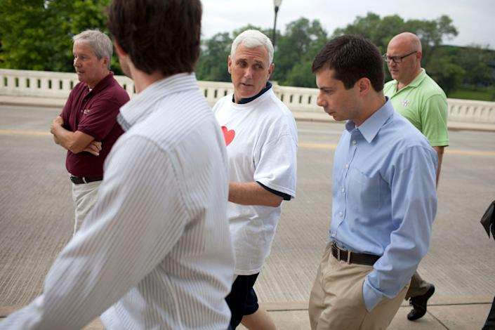 In this July 3, 2013, file photo, then-Indiana Gov. Mike Pence, center, talks with South Bend mayor Pete Buttigieg, right, as they cross the Jefferson Boulevard bridge during a fitness walk along the St. Joseph River in downtown South Bend, Ind.