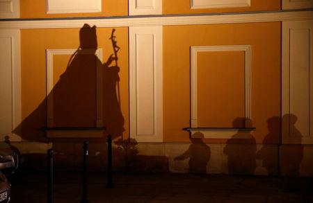 FILE PHOTO: People cast shadows as they pray in front of the statue of Pope John Paul II on the ninth anniversary of his death in Wadowice