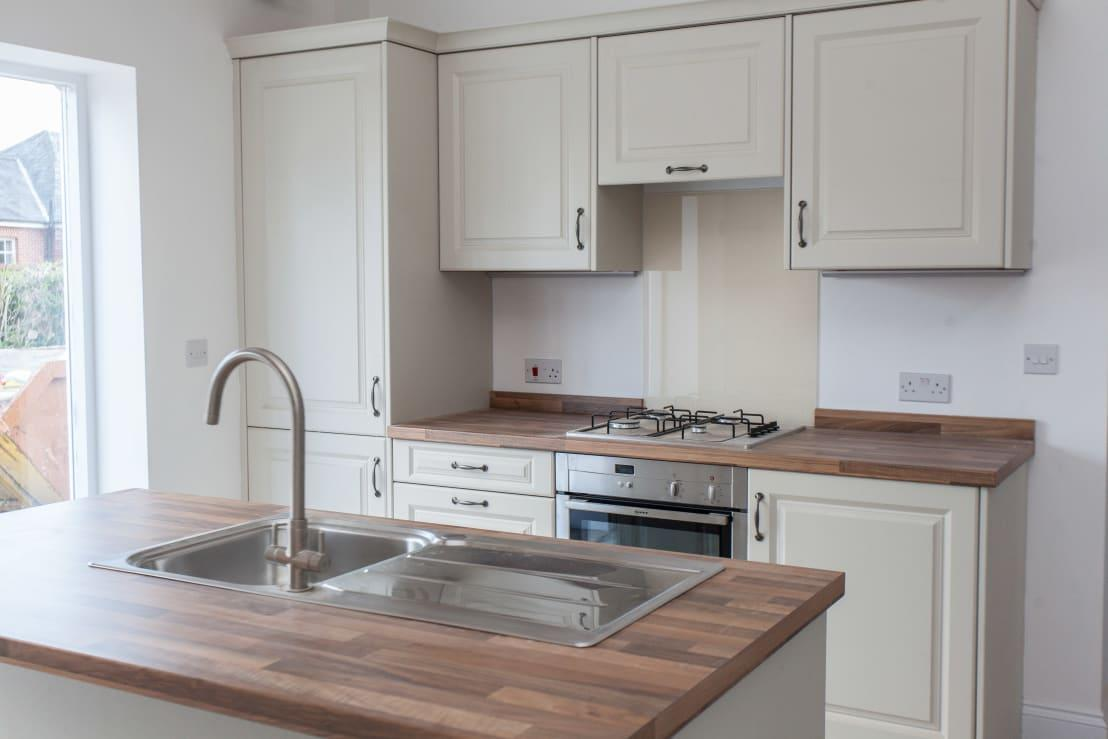 <p>Is this a brand new and modern kitchen? Yes, but by choosing Shaker style cabinet and drawer fronts, there is a wonderful little nod to the styling of the rest of the home. A simple and understated cream colour scheme works so well here and keeps all of the natural light flowing, while looking great with a natural wood counter. The only thing missing is an old school Aga, but we think the modern convenience of a gas stove is probably easier to cook with!</p>  Credits: homify / Hampshire Design Consultancy Ltd.