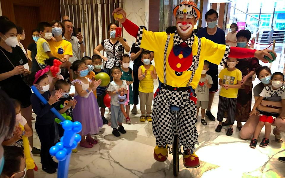Children wearing face masks to protect against the coronavirus watch a clown magician perform at a shopping mall - AP Photo/Mark Schiefelbein