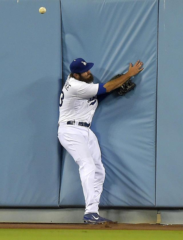 Los Angeles Dodgers center fielder Scott Van Slyke slams into the wall as he tries to catch a ball hit for an RBI double by San Diego Padres' Chase Headley during the fifth inning of a baseball game, Friday, July 11, 2014, in Los Angeles. (AP Photo/Mark J. Terrill)