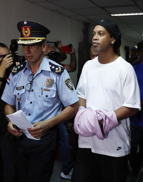 Former soccer star Ronaldinho walks handcuffed and escorted by a police officer to declare to judge Clara Ruiz Diaz at Justice Palace in Asuncion, Paraguay, Saturday, March 7, 2020. Ronaldinho and his brother Roberto were alleged to enter to the country with a false Paraguayan passport.(AP Photo/Jorge Saenz)