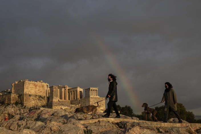 Women wearing face masks walk with their dogs at Areopagus hill, in front of ancient Acropolis hill, as a rainbow is seen in the cloudy Athenian sky, on Wednesday, March 31, 2021. (AP Photo/Petros Giannakouris)