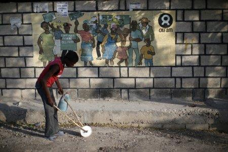 A boy playing with a homemade toy walks past an Oxfam sign in Corail, a camp for displaced people of the earthquake of 2010, on the outskirts of Port-au-Prince, Haiti, February 17, 2018. REUTERS/Andres Martinez Casares