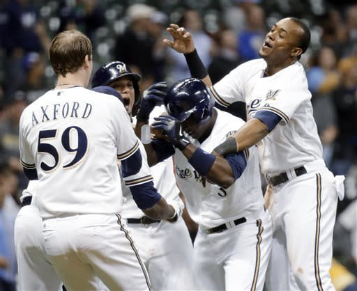 Milwaukee Brewers' Yuniesky Betancourt (3) is mobbed by teammates after driving in the game-winning run during the 10th inning of a baseball game against the Oakland Athletics on Tuesday, June 4, 2013, in Milwaukee. The Brewers won 4-3. (AP Photo/Morry Gash)