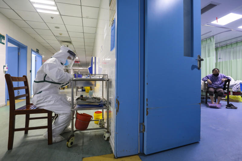 In this Thursday, Feb. 6, 2020, photo, a nurse takes notes in the isolation ward for 2019-nCoV patients at a hospital in Wuhan in central China's Hubei province. The number of confirmed cases of the new virus has risen again in China on Saturday, Feb. 8, 2020, as the ruling Communist Party faced anger and recriminations from the public over the death of a doctor who was threatened by police after trying to sound the alarm about the disease over a month ago. (Chinatopix via AP)
