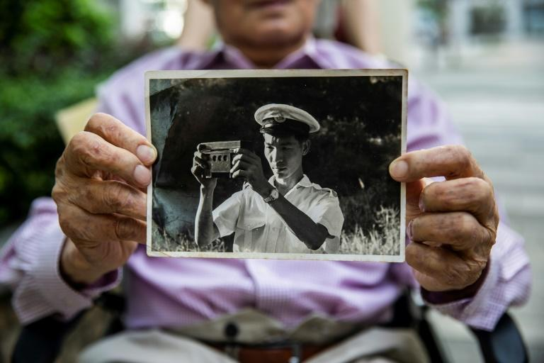 Lau holds a picture of himself from when he worked at Hong Kong's Water Supplies Department