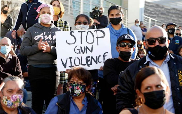 A girl holds a sign as people attend a vigil for the victims of a shooting at San Jose City Hall in San Jose, California - AFP