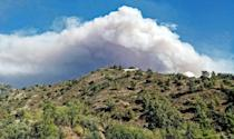A picture taken from near the village of Farmakas in the Nicosia district of Cyprus, shows heavy smoke billowing from behind the mountains as a giant fire rages in the Larnaca district of the island, on July 3, 2021