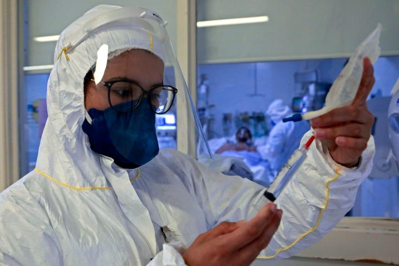 A health worker looks at a syringe as a patient infected with COVID-19 is treated at the Intensive Care Unit of the Santa Casa de Misericordia Hospital in Porto Alegre, Brazil, on August 13, 2020. - The occupancy of ICU beds by COVID-19 patients has risen and reached the highest mark since the beginning of the pandemic in Porto Alegre, where only a 9.4% of UCI beds remain empty. (Photo by SILVIO AVILA / AFP) (Photo by SILVIO AVILA/AFP via Getty Images)