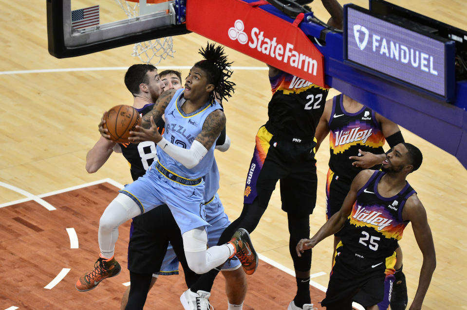 Memphis Grizzlies guard Ja Morant, front left, jumps to shoot ahead of Phoenix Suns forward Mikal Bridges (25) in the second half of an NBA basketball game Saturday, Feb. 20, 2021, in Memphis, Tenn. (AP Photo/Brandon Dill)