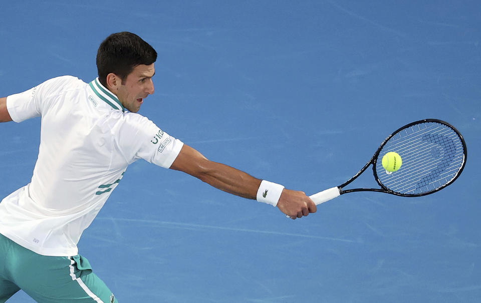 Serbia's Novak Djokovic hits a backhand to Russia's Daniil Medvedev during the men's singles final at the Australian Open tennis championship in Melbourne, Australia, Sunday, Feb. 21, 2021. (AP Photo/Hamish Blair)
