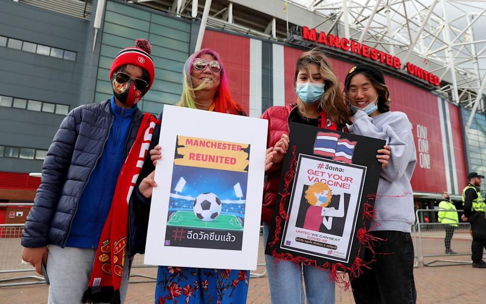 Fans pose for a photo outside the stadium while holding up a sign relating to COVID-19 Vaccines - GETTY