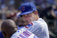 Chicago Cubs' Anthony Rizzo, right, talks with third base coach Willie Harris in the dugout during the seventh inning of a baseball game against the Cincinnati Reds Thursday, July 29, 2021, in Chicago. (AP Photo/Charles Rex Arbogast)
