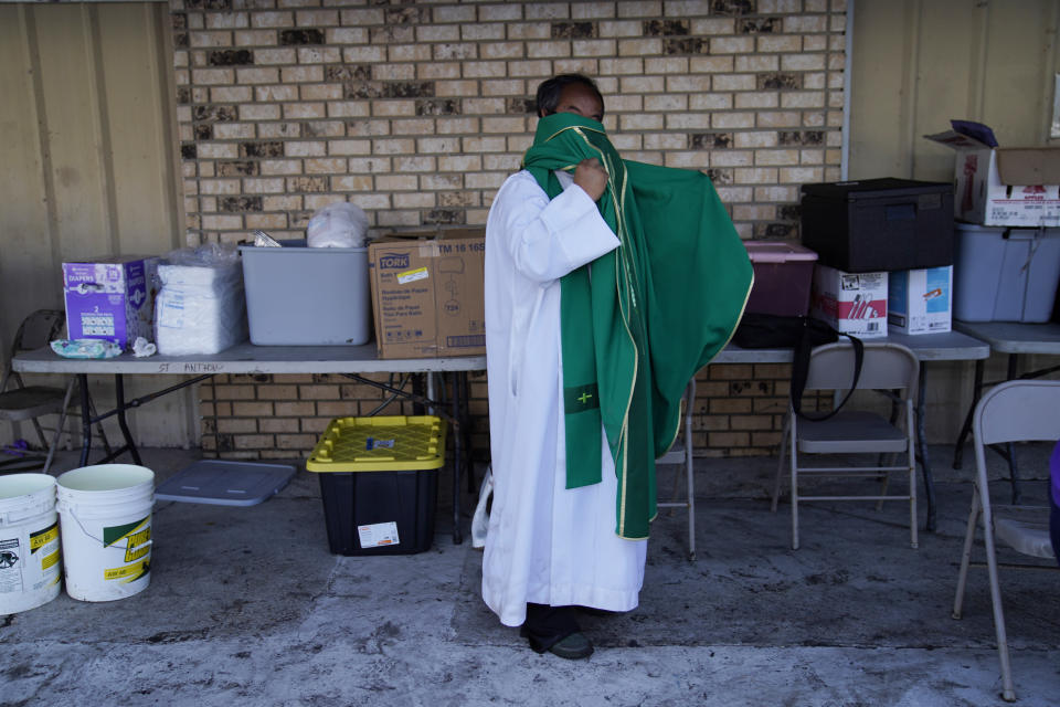 The Rev. Luke Nguyen prepares to celebrate a Mass in a parking lot in the aftermath of Hurricane Ida, Sunday, Sept. 5, 2021, in Jean Lafitte, La. The service was held in a parking lot after St. Anthony Catholic Church was flooded in the hurricane. (AP Photo/John Locher)