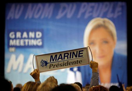 A supporter holds a poster to support Marine Le Pen, French National Front (FN) political party leader and candidate for French 2017 presidential election, during a political rally in Perpignan, France, April 15, 2017.  REUTERS/Jean-Paul Pelissier