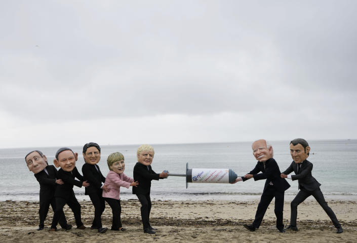 Activists wearing giant heads of the G7 leaders tussle over a giant COVID-19 vaccine syringe during an action on the beach in Falmouth, Cornwall, England, during an action by NGO's on Friday, June 11, 2021. Leaders of the G7 begin their first of three days of meetings on Friday in Carbis Bay, in which they will discuss COVID-19, climate, foreign policy and the economy. Depicted from left to right, Italy's Prime Minister Mario Draghi, Japan's Prime Minister Yoshihide Suga, Canadian Prime Minister Justin Trudeau, German Chancellor Angela Merkel, British Prime Minister Boris Johnson, U.S. President Joe Biden and French President Emmanuel Macron. (AP Photo/Kirsty Wigglesworth)