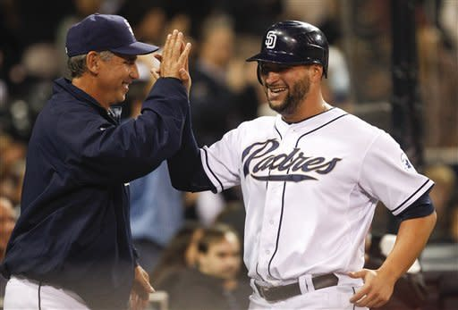 San Diego Padres' Yonder Alonso high fives with manager Bud Black after scoring in the ninth against the Colorado Rockies during a baseball game Tuesday, May 8, 2012 in San Diego. (AP Photo/Lenny Ignelzi)
