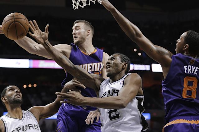 San Antonio Spurs' Kawhi Leonard (2) is blocked by Phoenix Suns' Miles Plumlee, center, during the first half of an NBA basketball game, Wednesday, Nov. 6, 2013, in San Antonio. Spurs' Tim Duncan, left, and Suns' Channing Frye (8) also take part in the play. (AP Photo/Eric Gay)