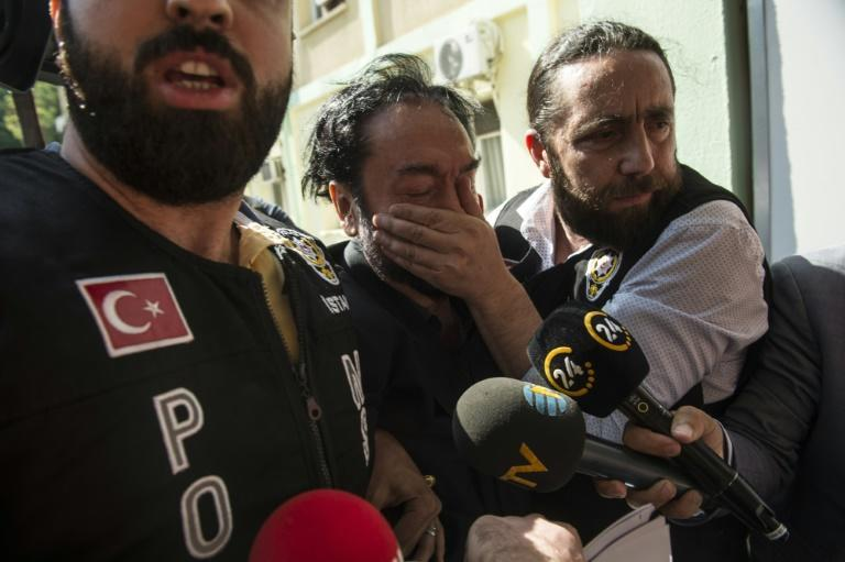 Cult leader: A Turkish police officer puts his hand over the mouth of televangelist Adnan Oktar, who was jailed Monday for 1,075 years for sexual assault