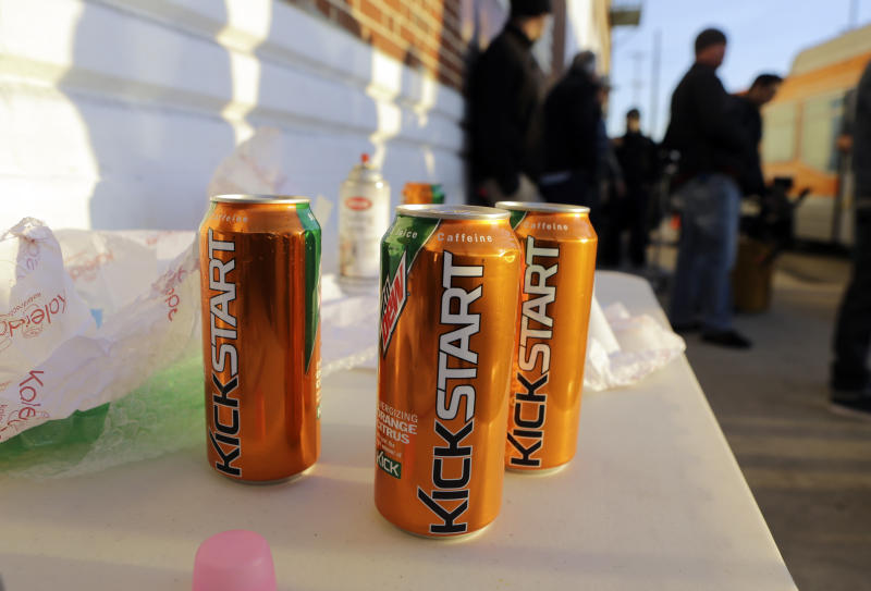 Product cans are on display during the filming of a commercial for a new PepsiCo product called Kickstart, a carbonated drink that is part juice with Mountain Dew flavor, on the streets of downtown Los Angeles Tuesday, Jan. 29, 2013.  PepsiCo Inc. is set to roll out the new drink called Kickstart this month that has Mountain Dew flavor but is made with 5 percent juice and an extra jolt of caffeine and Vitamins B and C. The company is hoping to grow sales by reaching Mountain Dew fans at a new time of day: morning.  (AP Photo/Reed Saxon)