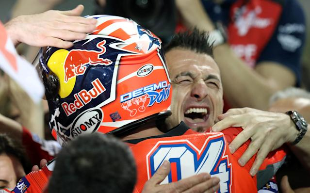 Motorcycle Racing - Qatar Motorcycle Grand Prix - MotoGP race - Losail, Qatar - March 18, 2018 - Ducati Team rider Andrea Dovizioso of Italy is hugged by a team member as he celebrates after winning the race. REUTERS/Ibraheem Al Omari