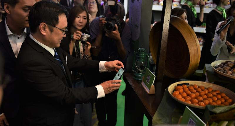 YB Tuan Chong Chieng Jen, Deputy Minister of Domestic Trade and Consumer Affairs, trying out the conceptualised payment method at street store in the Experience Zone.