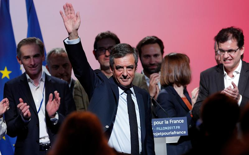 Francois Fillon waves as he arrives to deliver his speech during a campaign meeting in Aubervilliers, outside Paris, France, Saturday, March 4 - Copyright 2017 The Associated Press. All rights reserved.